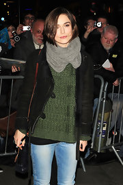 Keira stays bundled in a gray knit scarf and emerald green sweater while posing for fans in London.