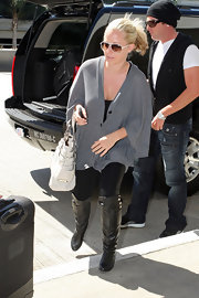 Kendra kicked off her trip in a comfy overssized sweater, black leggings and a pair of black leather over the knee boots.