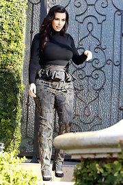 Kim Kardashian showed off her awesome cuves with a fitted black turtleneck and high-waisted print pants.