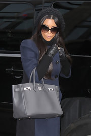 Kim paired her navy trench coat and knit beanie with fingerless leather gloves.