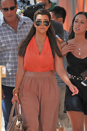 Kourtney looked '70s-chic in this orange silk blouse and wide-leg trousers.