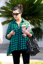 "Kourtney is wearing a glamorous pair of black cateye ""Night Moves"" sunglasses. This feminine style is great on most face shapes."
