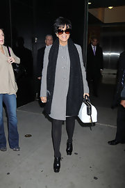 Kris Jenner matched her eye-catching checkered swing coat with a structured two-tone satchel.