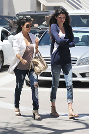 Kendall Jenner wore a pair of distressed capri jeans, paired with gladiator sandals.