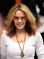 Kylie Minogue showed off her designer duds in a pair of orange tinted shades, which sure came in handy with all those flash bulbs going off.