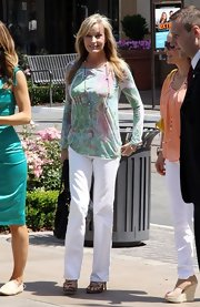 Bo Derek wore classic white jeans with a colorful print blouse for a summer-chic look.