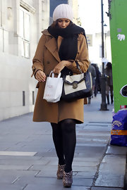 Leona bundled up in a wool coat and animal print ankle boots.