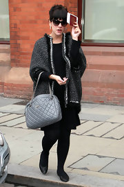 Lily Allen paired her all black ensemble with a tweed embellished cape coat.