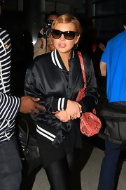 Lindsay Lohan traveled in style with this black satin, letterman-style jacket.