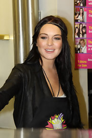 While making another chaotic appearance Lindsay Lohan shows off her boho-vibe with her sleek center part and simple headband.