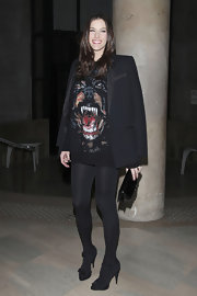Liv Tyler paired her risque tunic with opaque tights and black suede sandals.