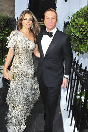 Elizabeth Hurley added subtle shine to her fluttery animal print gown with a gold tube clutch.