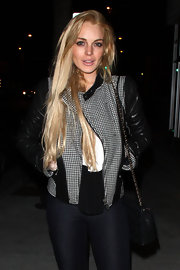 Lindsay poses on the street in a leather jacket with hounds tooth contrasting fabric.