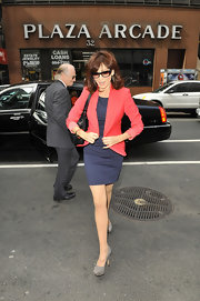 Marilu added a bit of color to her navy dress with this solid red blazer.