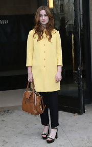 Alice Englert's canary yellow coat was springtime appropriate at the Miu Miu fashion show in Paris.