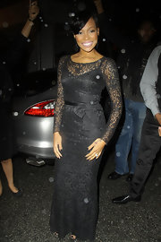 The songstress wears a vintage inspired floor length lace gown with long sleeves and a darling bow detail at the waist.