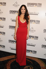 Catt wears a floor length red evening gown with a deep plunge and revealing back for the Cosmo party.