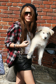 Miley looks chic and stylish in her crocheted black beret with silver star embellishments. P.S. Nice leather shorts!