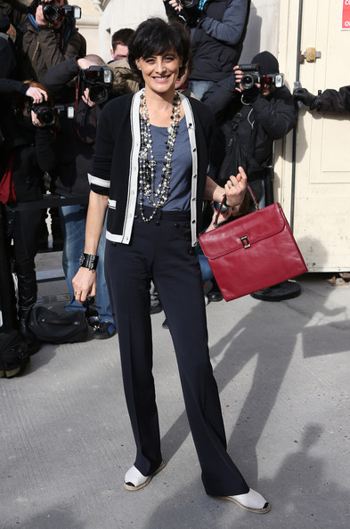 Ines de la Fressange looked smart wearing a cardigan and slacks ensemble styled with a red leather briefcase.