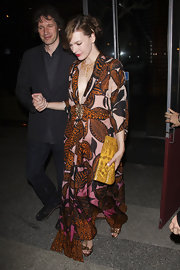 Milla channeled the '70s with a mustard colored snakeskin clutch. She paired the bow-adorned bag with a floral caftan.