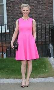 Emilia looked pretty in pink in this sleeveless frock with black trim.