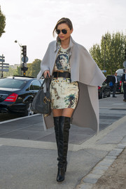 Miranda Kerr looked very high-fashion in a gray cape teamed with a print dress and thigh-high boots during a trip to Paris.