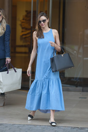 Miranda Kerr looked very summery in a loose blue dress with a flared hem while out shopping in Paris.