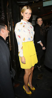 Mischa wore a playful beetle print blouse with her bright yellow skirt for a night out in London.