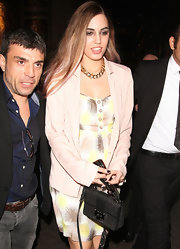 Amber Le Bon arrived at the launch of Eleven Paris Store with a small flap-closure shoulder bag on hand.