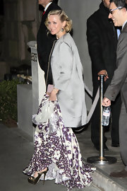 Naomi was the picture of class in this silver streamlined evening coat over her floral winter dress.