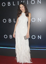 Olga Kurylenko chose this white column-style evening gown with embroidered lace detailing and a feathered skirt.
