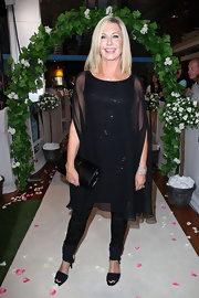Olivia Newton-John arrived at a movie premiere wearing an all-black outfit including a pair of black sandals.
