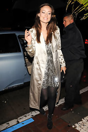 Olivia wears a metallic trench for her dinner date.