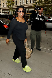 When your name is Oprah Winfrey, there's no need to wear real shoes. The renowned talk show host wore these fuzzy frog slippers for a day filled with shopping.