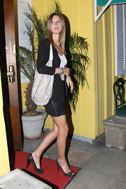 The black and white clad heiress made a quick getaway carrying a hot white leather studded hobo bag.