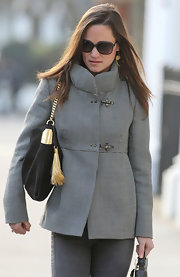 Pippa Middleton accented her houndstooth jacket with a black tasseled purse.
