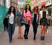 Frankie Sandford posed with her group mates in a flirty leather mini skirt and a color-block top.