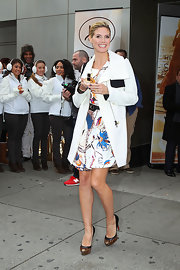 Heidi Klum winterized her darling white print dress with a white shawl collar coat with black trim.