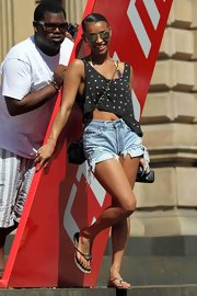 The toned songstress sported cut off denim shorts and a pair of casual flip flops with a gold designer logo.