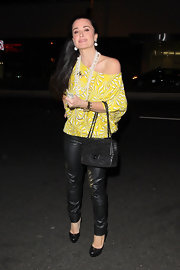 Kyle Richards toughened up her yellow blouse with skinny leather pants.