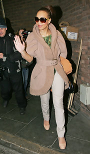 Rebecca Ferguson waves to fans in chic nude platform pumps. She paired the heels with white skinny jeans and a belted sheepskin coat.