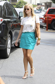 Reese chose a floral-printed blouse to pair with her turquoise mini skirt for a polish every day look.