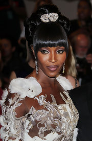Naomi Campbell accented her coif with a 1930's diamond brooch in platinum.