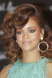 Rihanna wore some statement making gold hoops with her aqua feathered ensemble at the launch of her fragrance, Reb'l Fleur.
