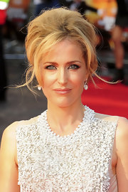 Gillian Anderson wore a done-up 'do at the UK premiere of 'Johhny English Reborn'. To recreate her look, begin by backcombing everywhere. The idea is to get lots of texture and volume. Next, section out the bangs and crown then pull tresses back, twisting up from the nape of the neck. Hold the twist in place and very gently run a comb or brush over the hair to smooth it slightly then secure it in place using either bobby pins or u-shaped hair pins. Finally, hair from the crown is pulled back loosely to maintain volume, and incorporated into the twist. Bangs can be left free like Gillian's, swept across the forehead or pushed back behind the ears.