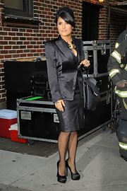 Shining from head-to-toe, Salma Hayek paired satin platform pumps with her sleek black skirt suit.