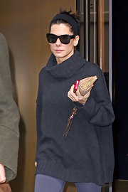 Sandra Bullock keeps her hair back with a black cloth headband while running errands in NYC.