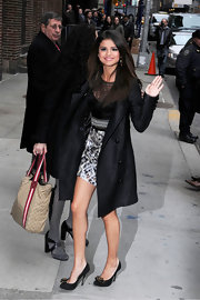 Selena waved to adoring fans outside of the David Letterman show in a sleek black coat over her mini dress.