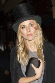 Sienna Miller accessorized with a classic black satin clutch for the AnOther Magazine party.