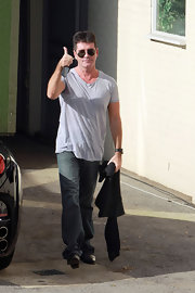 Simon wore a baggy gray v-neck tee on his way to work.